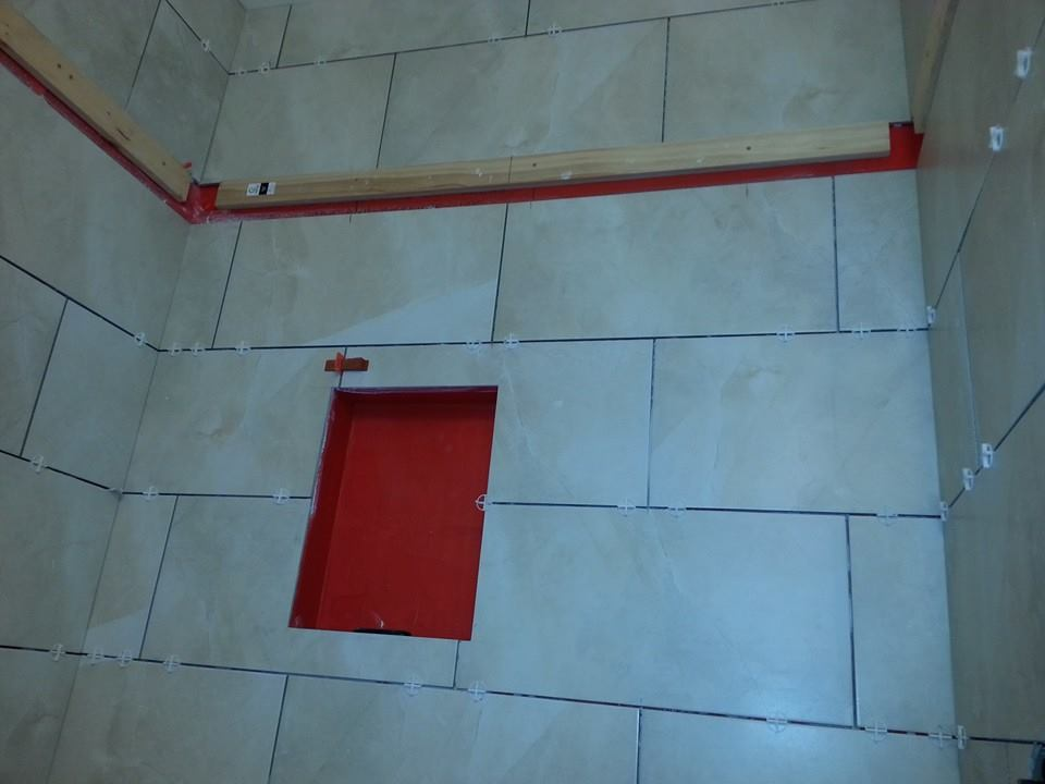 building tile shower walls and prepping to add a mosaic banner