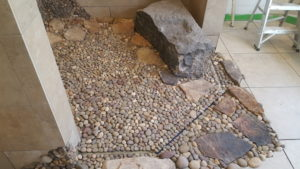 tile top linear drain with river rock and stone.
